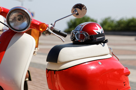 Moto helmet and glasses on the retro motor scooter seat on blurred background