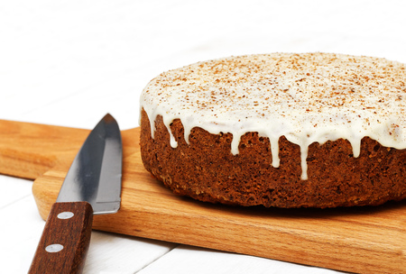Closeup homemade sweet carrot cake with walnuts, cinnamon and white icing on white wooden table