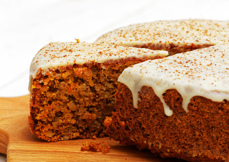 Closeup homemade sweet carrot cake with walnuts, cinnamon and white icing on white wooden table 版權商用圖片 - 84983590