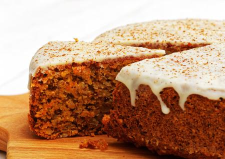 Gâteau de carotte douce CloseUp maison avec des noix, de la cannelle et du glaçage blanc sur une table en bois blanc Banque d'images - 84983590