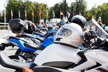 Light silver moto helmet on motorcycle and motorbikes on blurred background Фото со стока