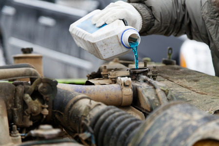 An auto mechanic pours antifreeze into the radiator of an old car engine. Shallow focus. Stock Photo