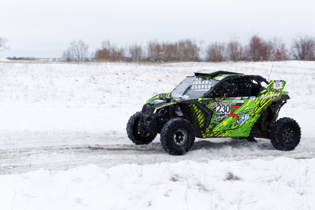 Ulyanovsk, Russia - December 09, 2017. Winter rally raid Hills of Russia. Four wheel drive ATV vehicle rushes on the snow-covered road among fields and hills.