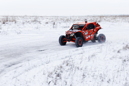 Ulyanovsk, Russia - December 09, 2017. Rally raid Hills of Russia. Four wheel drive ATV vehicle rushes on the snow-covered road among fields and hills.