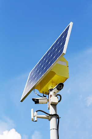 Two security cameras and solar panel on the post against blue sky on background Archivio Fotografico
