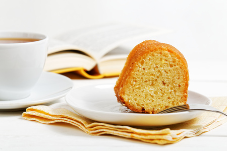 Closeup piece of homemade lemon cake and cup of tea on white wooden table. Open book on blurred background. Shallow focus. 免版税图像