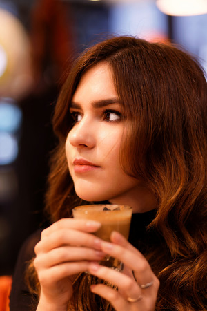 Portrait of a young girl holding a cup of coffee flat white in her hand and smiling while looking directly into the camera. Shallow focus and blurred background. Stock Photo