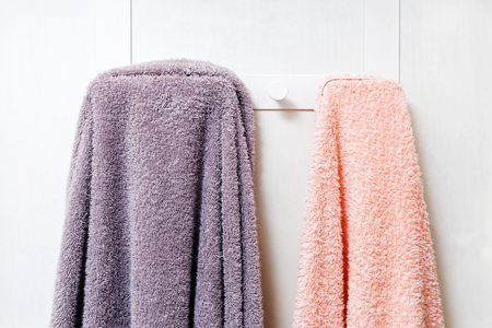 Closeup photo of two terry towels hanging on the white wall