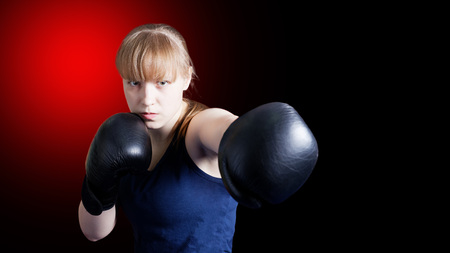 Sporty girl doing boxing exercises, making direct hit isolated on black background witn red spot. Copyspace.