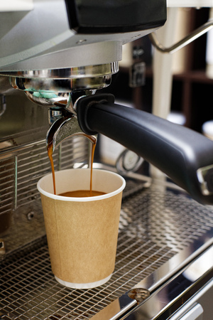 Closeup of espresso pouring from coffee machine in cardboard cup for take away. Shallow focus.