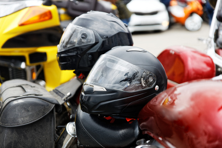 Motorcycle helmets lying on the seats of a motorcycles against blurred background