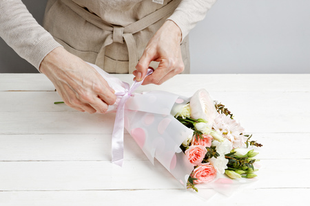 Closeup hands of woman florist decorate a bouquet of flowers on white wooden table Zdjęcie Seryjne