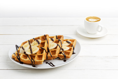 Homemade belgian waffles with banana slices topped with chocolate and cup of coffee on white wooden table. Shallow focus. Copyspace. Stockfoto