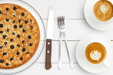 Two cups of coffee and homemade pie with cottage cheese souffle decorated with almonds and blueberries on white wooden table. Top view. Imagens