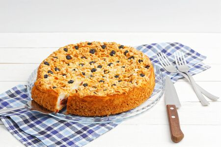 Homemade pie with cottage cheese souffle and plum decorated with almonds and blueberries on white wooden table. Angle view. Copyspace. Imagens