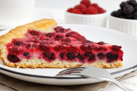 A piece of homemade pie with red and black raspberries on white wooden table. Shallow focus.