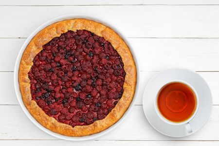 Homemade galette with red raspberries and black currants and cup of tea on white wooden table. Top view.