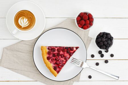 A cup of coffee and piece of homemade pie with red and black raspberries on white wooden table. Top view. Imagens