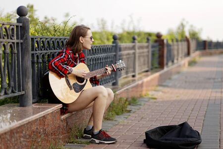 Ulyanovsk, Russia - July 26, 2019: Street musician young woman playing acoustic guitar and singing in a city park