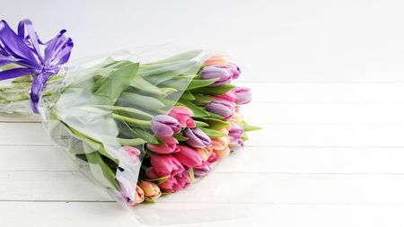 A bouquet of flowers colorful tulips on a white wooden table.