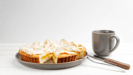 Homemade apricot pie decorated with meringue and a mug of tea on a white wooden table. Copyspace. Imagens