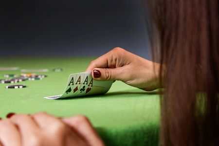 Woman playing poker game and looking at cards. Green table, chips and four aces cards in hand. Shallow focus.