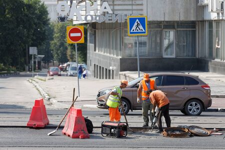 Ulyanovsk, Russia - July 27, 2019: Road workers with a shovel and pneumatic hammer drill equipment repairing street during roadworks