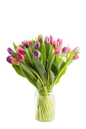 Bouquet of spring tulips flowers in a transparent glass jar isolated on white Imagens