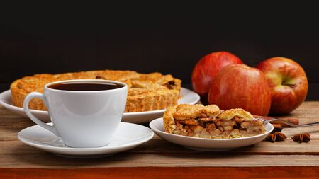 Homemade apple pie with cinnamon and cup of tea on wooden table. Shallow focus. Imagens