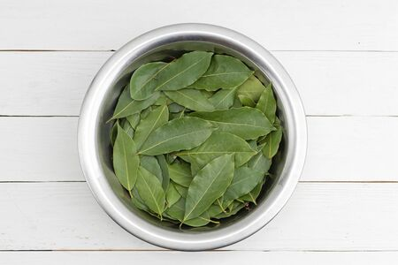 Bay leaves in a metal bowl on white wooden table. Top view. Imagens