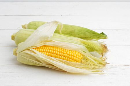 Three ripe ears of corn on white wooden table