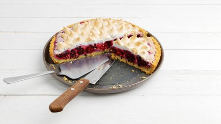 Homemade berry pie with meringue on white wooden table Imagens