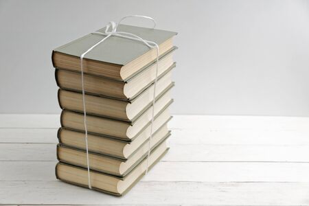 Stack of old books tied with white twine on white wooden table. Imagens