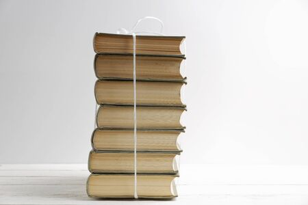 Stack of old books tied with white twine on white wooden table. Front view.