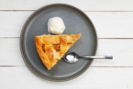 Piece of an apple pie with ice cream on white wooden table. Top view.