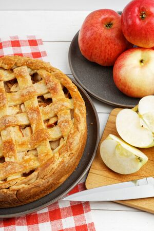Homemade apple pie with lattice and apples on white wooden table. Shallow focus. 스톡 콘텐츠