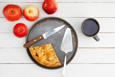 Homemade apple pie with lattice, apples and cup of tea on white wooden table. Top view.