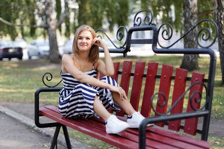 Portrait of a young attractive smiling girl sitting on a park bench. Blurred background. Shallow focus.