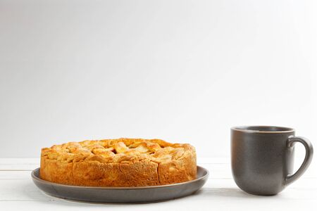 Homemade apple pie with lattice and cup of tea on white wooden table. Shallow focus. Front view. Copyspace. 스톡 콘텐츠