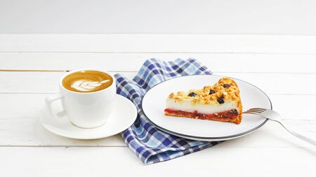 Cup of coffee and piece of homemade cake with cottage cheese souffle and plum decorated with almonds and blueberries on white wooden table