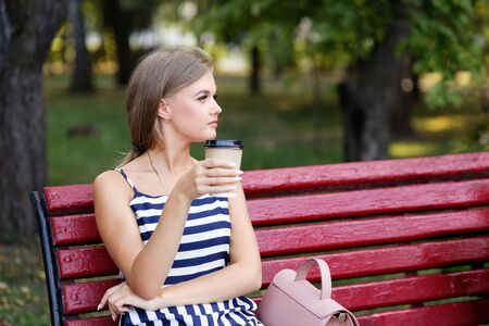 Young girl sitting alone on a park bench and drinking coffee from a cardboard cup. Shallow focus.
