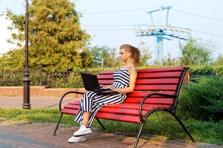 Girl and laptop. Young girl is using laptop while sitting on a park bench 스톡 콘텐츠