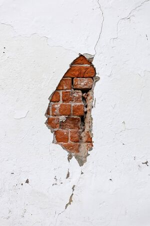 Old cracked white wall with broken plaster through which red bricks are visible