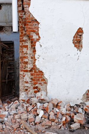 Corner of a destroyed building with a damaged wall and a pile of broken brick