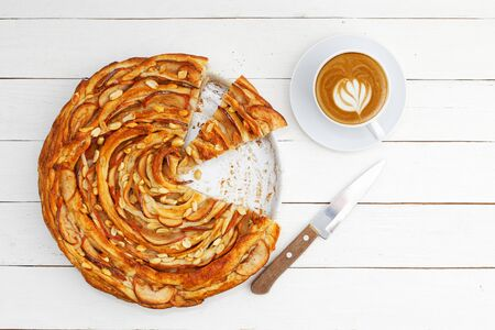 Fresh baked homemade apple and cinnamon puff pastry swirl pie and cup of coffee on white wooden table. Top view.