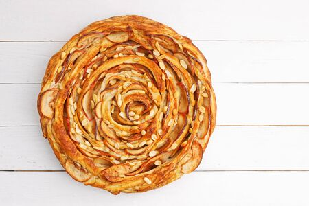 Fresh baked homemade puff pastry swirl pie with apple, cinnamon and peanut on white wooden table. Top view. Copyspace. 스톡 콘텐츠