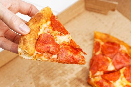 Closeup slice of italian pepperoni pizza in hand and open box with pizza leftovers on blurred background 스톡 콘텐츠