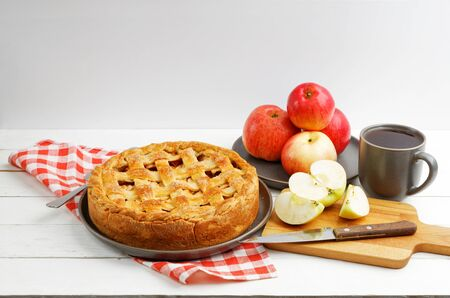 Homemade apple pie with lattice, apples and cup of tea on white wooden table. Angle view. Copyspace.