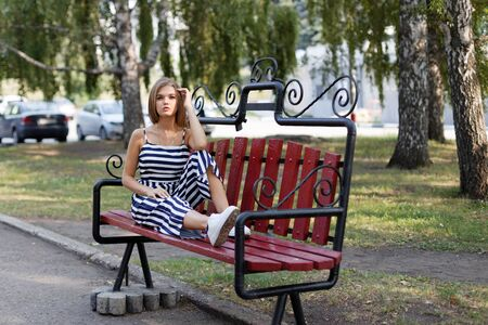 Young attractive girl sitting alone on a park bench 스톡 콘텐츠