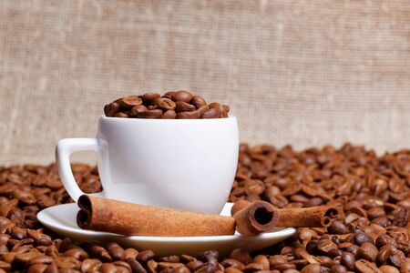 Coffee cup demitasse full of coffee beans and cinnamon sticks in the heap coffee beans on burlap background 스톡 콘텐츠